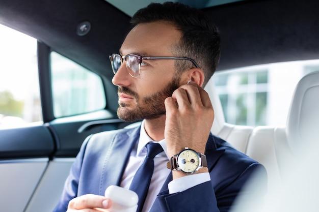 Man die een koptelefoon neemt. bebaarde man met een bril die een koptelefoon neemt terwijl hij in zijn auto zit