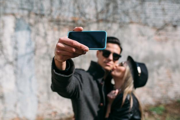 Man die een kus van zijn vriendin tijdens het nemen van een foto