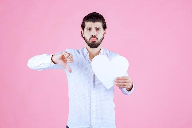 Man die een leeg hartcijfer houdt en duim naar beneden toont.