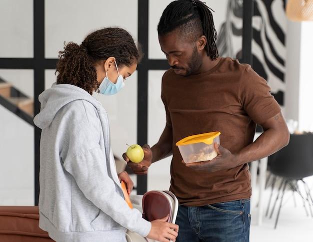 Man die een lunchdoos geeft aan zijn dochter