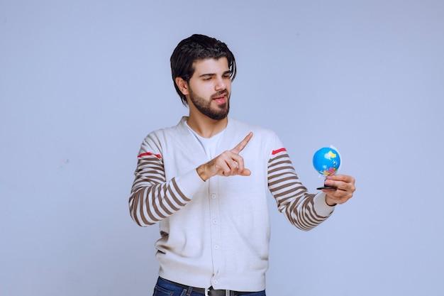 Man die een mini-wereldbol vasthoudt, deze schudt en probeert een locatie te raden.