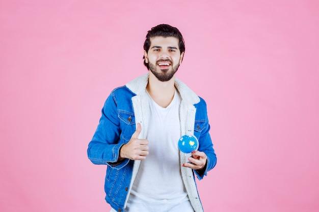 Man die een mini-wereldbol vasthoudt en een teken van plezier toont