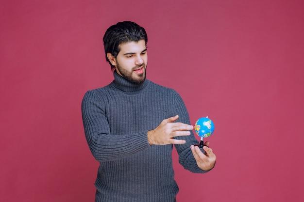 Man die een mini-wereldbol vasthoudt en er een presentatie over maakt.