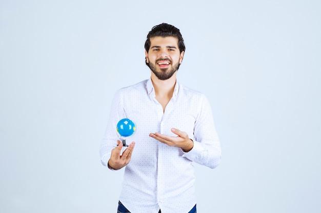Man die een mini-wereldbol vasthoudt en ernaar kijkt
