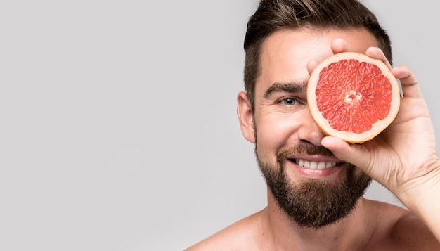 Man die een oog bedekt met een gehalveerde grapefruit