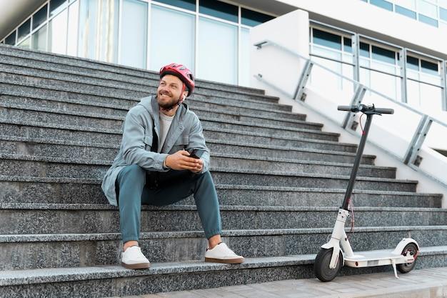 Man die een pauze neemt na het rijden op zijn scooter