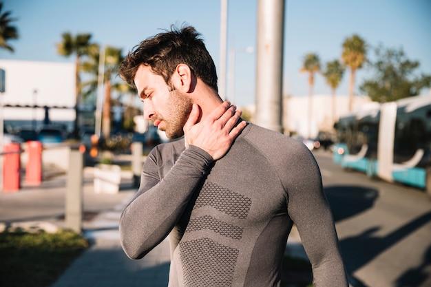 Man die een pijnlijke nek masseert