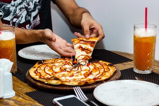 Man die een plakje kip pizza