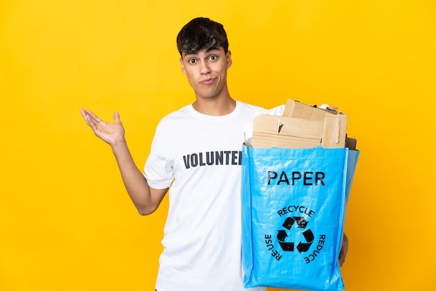 Man die een recyclingzak vol papier houdt om over geïsoleerde gele muur te recyclen met twijfels terwijl hij zijn handen opheft