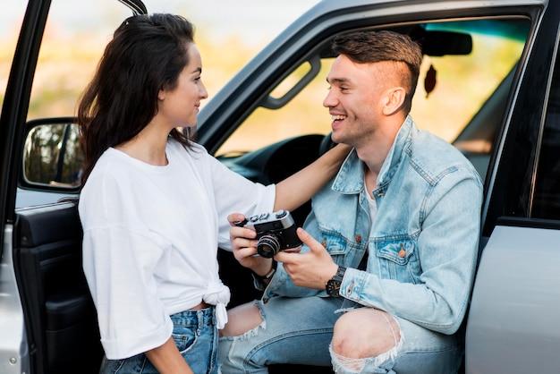 Man die een retro camera houdt en zijn vriendin bekijkt
