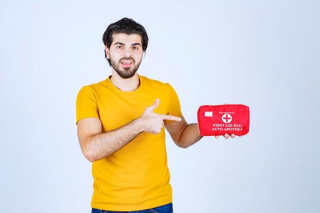 Man die een rode ehbo-kit vasthoudt en promoot.