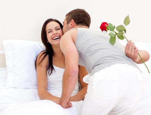 Man die een roos en een zoen geeft aan zijn mooie vrouw