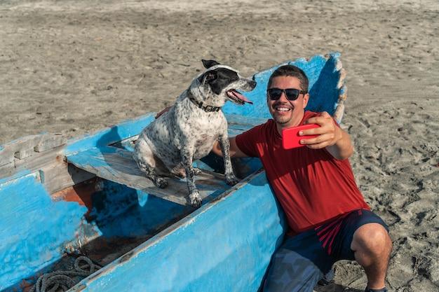 Man die een selfie maakt met zijn hond op het strand in de zomer