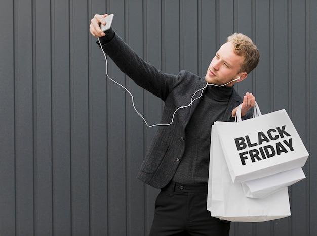 Man die een selfie maakt terwijl hij zwarte vrijdag-boodschappentassen vasthoudt