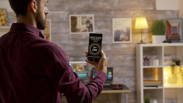 Man die een slimme lichten-app gebruikt om de lichten in de woonkamer aan te doen. slimme technologie en toepassing