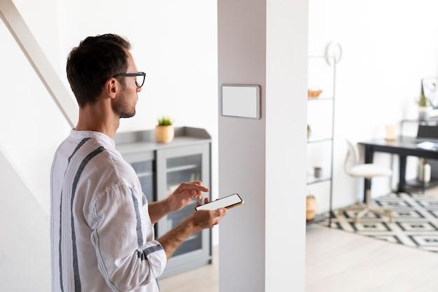 Man die een smartphone gebruikt in zijn geautomatiseerde huis