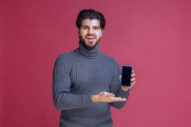 Man die een smartphone vasthoudt en deze presenteert aan de klanten.