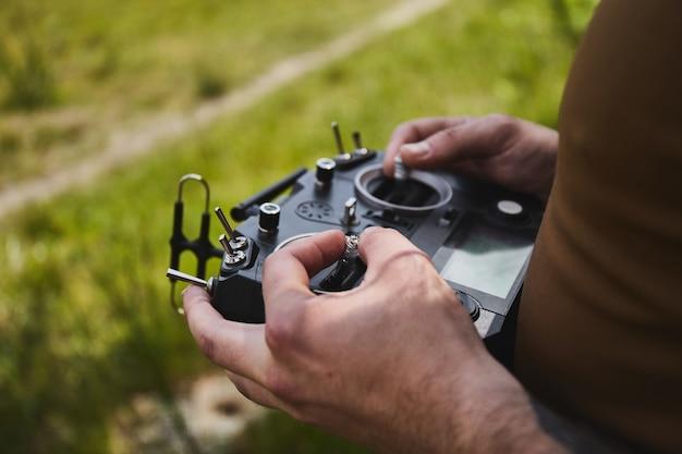 Man die een snelle race-drone bestuurt met een afstandsbediening, een quadcopter-drone op afstand