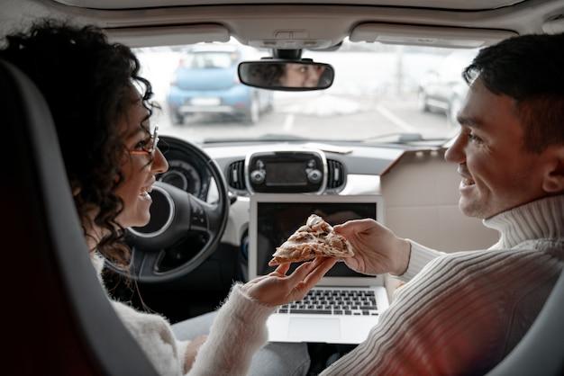 Man die een stuk pizza geeft aan een meisje in de auto. krullende jonge vrouw draagt een bril. gelukkige europese paarontspanning in de autocabine. concept van samen genieten van tijd