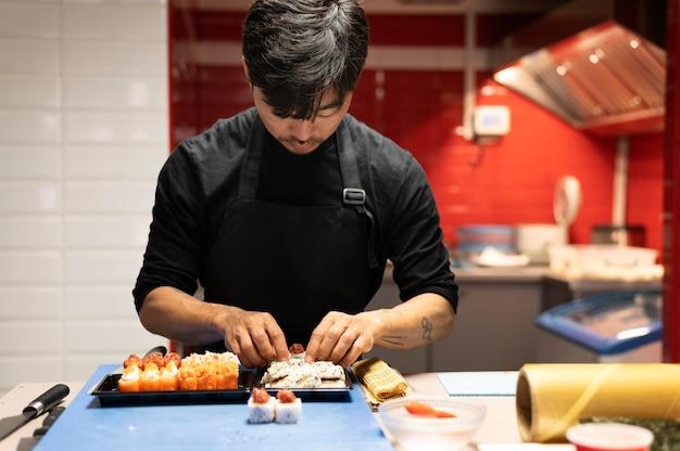Man die een sushi-bestelling klaarmaakt voor een afhaalmaaltijd