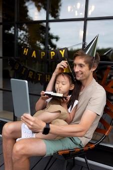 Man die een videogesprek voert met zijn vrouw op de verjaardag van hun dochter