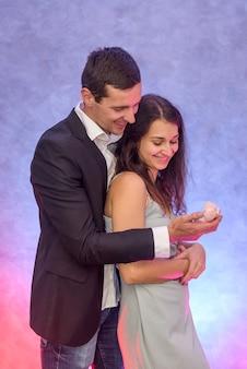 Man die een voorstel doet aan zijn vriendin die haar gouden ring met diamant laat zien