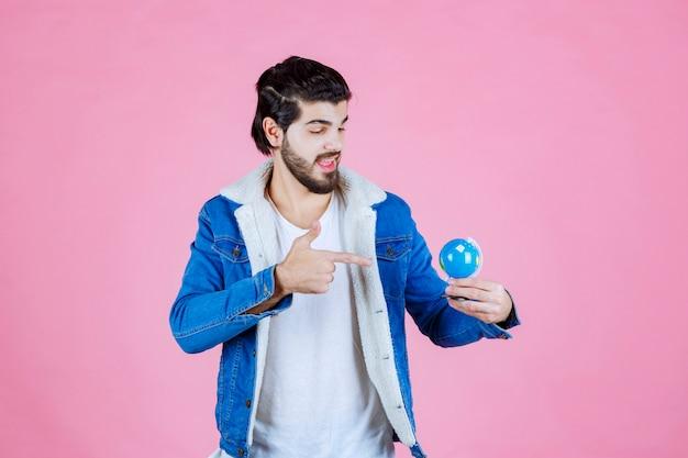 Man die een wereldbol vasthoudt en een locatie probeert te vinden
