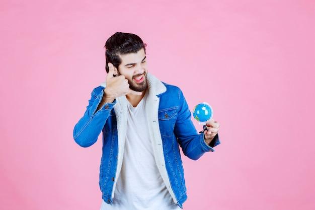 Man die een wereldbol vasthoudt en om een telefoontje vraagt