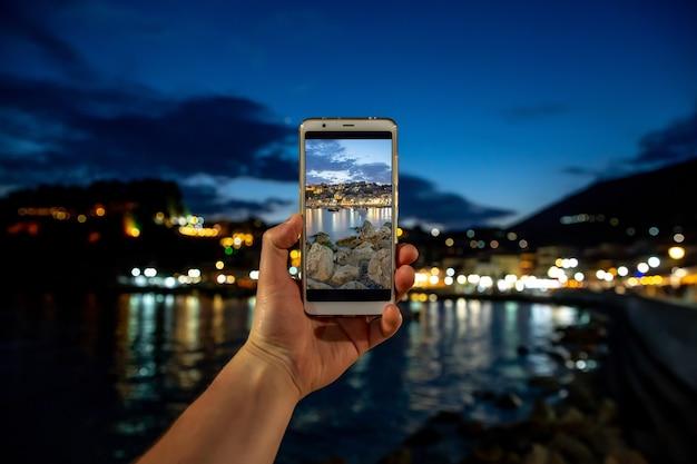 Man die foto op mobiele telefoon, smartphone bij avond zee stad