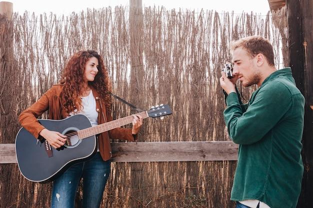 Man die foto's van vrouw het spelen gitaar neemt