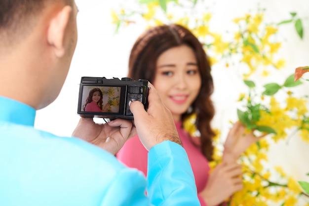 Man die foto van jonge aziatische vrouw in traditionele kledij met bloeiende mimosa nemen