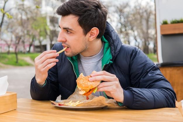Man die gebakken aardappelen eet met een hamburger in straatvoedselcafé