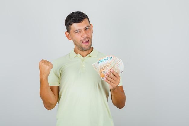 Man die gebalde vuist met bankbiljetten in t-shirt opheft en gelukkig kijkt