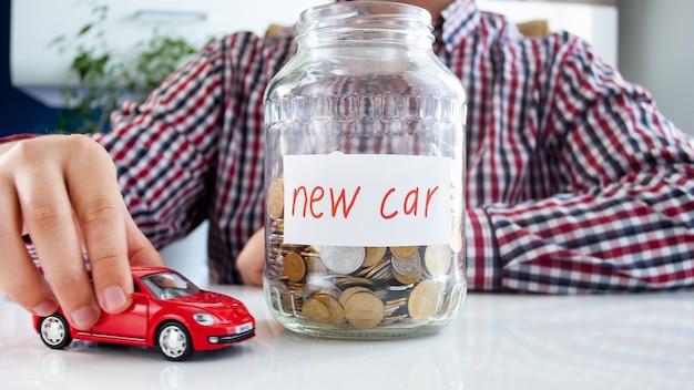 Man die geld inzamelt voor het kopen van een nieuwe auto. concept van financiën, economische groei en banksparen.