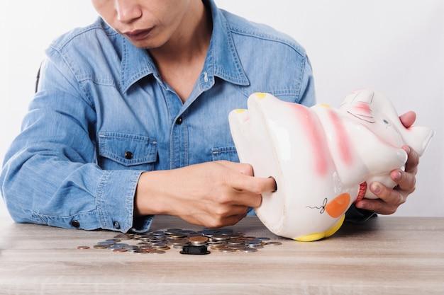 Man die geld uit spaarvarken optelt of container op bureau opbergt
