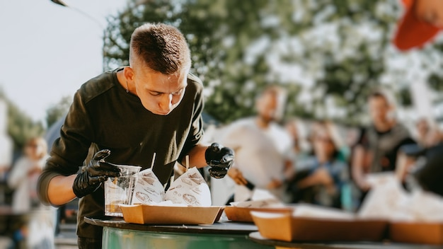 Man die geniet van een straatvoedselfestival in de buitenlucht, een bier- en hamburgerevenement. burger battle