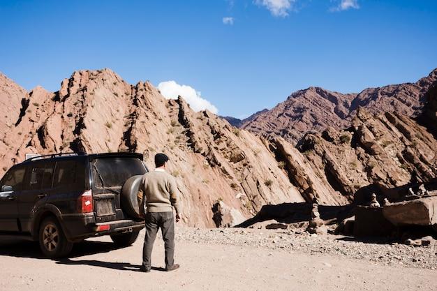 Man die geniet van het uitzicht op de bergen