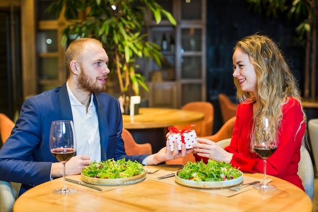 Man die geschenkdoos geeft aan blonde vrouw aan tafel