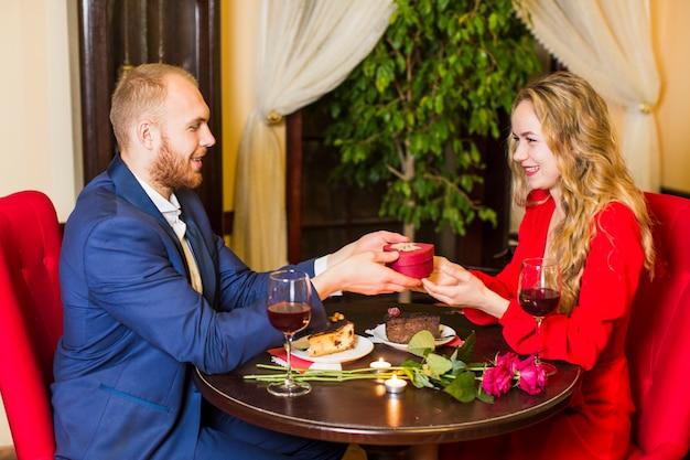Man die geschenkdoos in hartvorm geeft aan vrouw aan tafel