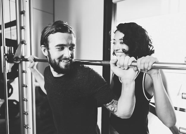 Man die gewichtheffen met barbell uitoefent bij fitness gym