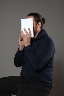 Man die gezicht bedekt met boek tijdens het lezen op grijze muur