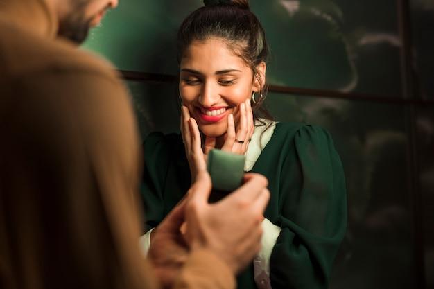 Man die gift in vak presenteert aan gelukkige vrouw