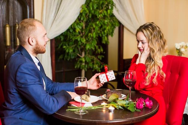 Man die giftdoos geeft aan vrouw bij lijst in restaurant