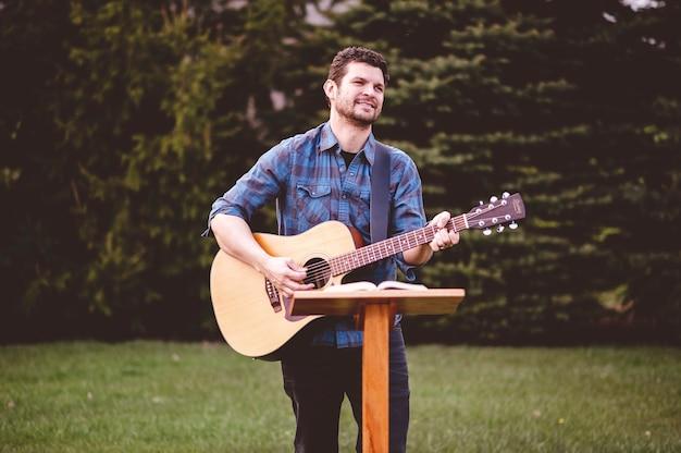 Man die gitaar speelt in het park