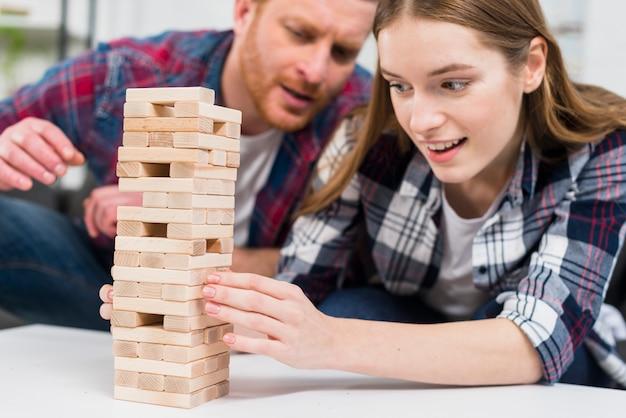 Man die glimlachende jonge vrouw bekijkt die de houten bloktoren op witte lijst in evenwicht brengt