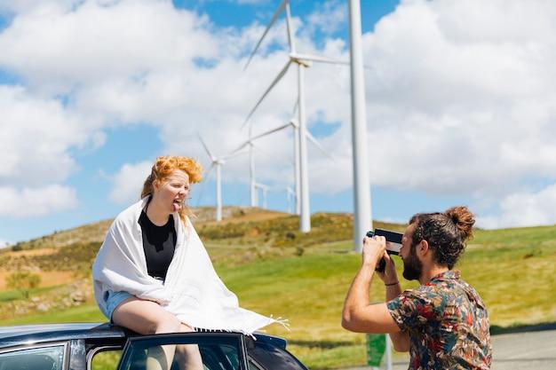 Man die grijnzende vrouw in witte sjaalzitting op autodak fotograferen