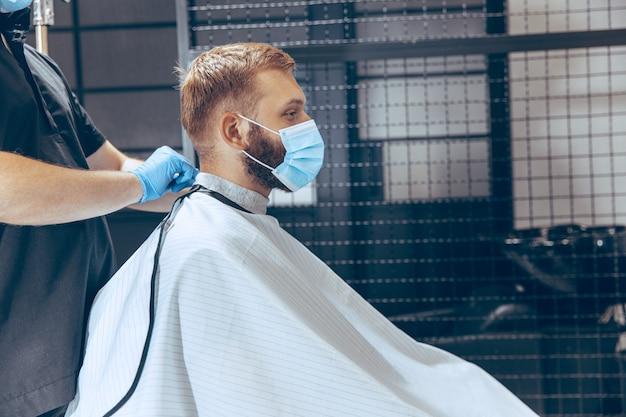 Man die haar laat knippen in de kapperszaak met een masker tijdens de pandemie van het coronavirus. professionele kapper die handschoenen draagt. covid-19, schoonheid, zelfzorg, stijl, gezondheidszorg en geneeskundeconcept.
