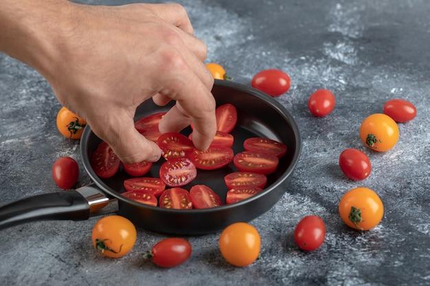 Man die half gesneden cherrytomaat uit koekenpan neemt.