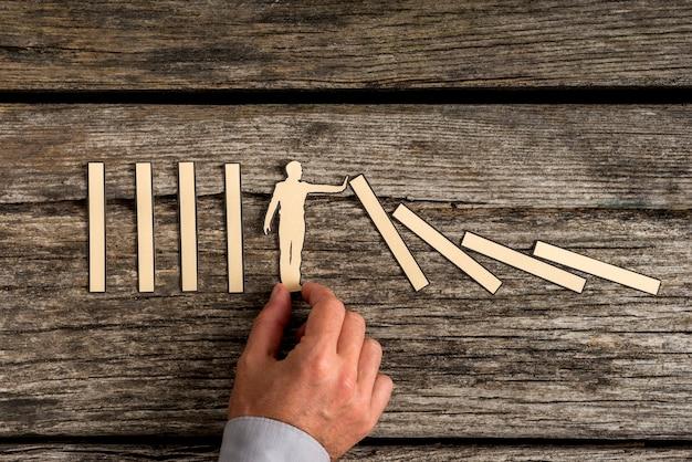 Man die het domino-effect stopt met een uitgesneden silhouet van papier op een rustiek hout