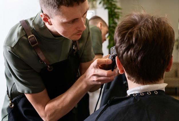 Man die het haar van een klant knipt